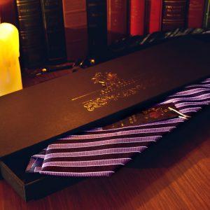 """Fialová Pásikavá Hodvábna Pánska Kravata S Čiernym Pásikom[hr color=""""#ddc49d"""" style=""""gradient"""" size=""""1px""""] Ručne vyrábana hodvábna kravata pre náročných. Materiál: 100% Hodváb Rozmer: 150 x 10 cm Farba: Modrá, Červená, Biela Vzor: Pásikavý Súčasťou objednávky je luxusné darčekové balenie RDB Royal."""